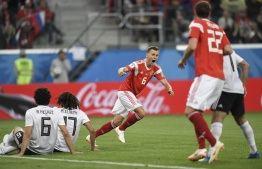 Russia's midfielder Denis Cheryshev (C) reacts after scoring the 2-0 goal during the Russia 2018 World Cup Group A football match between Russia and Egypt at the Saint Petersburg Stadium in Saint Petersburg on June 19, 2018.  / AFP PHOTO / GABRIEL BOUYS /