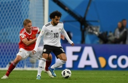 Russia's midfielder Yuri Gazinskiy (L) vies with Egypt's forward Mohamed Salah during the Russia 2018 World Cup Group A football match between Russia and Egypt at the Saint Petersburg Stadium in Saint Petersburg on June 19, 2018.  / AFP PHOTO / Olga MALTSEVA /