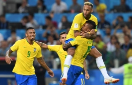 Brazil's midfielder Paulinho (R) celebrates with teammates Brazil's forward Neymar (top), Brazil's forward Gabriel Jesus (L) and Brazil's forward Philippe Coutinho after scoring during the Russia 2018 World Cup Group E football match between Serbia and Brazil at the Spartak Stadium in Moscow on June 27, 2018. / AFP PHOTO / Francisco LEONG /