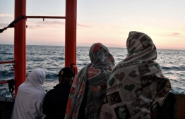 Migrants stand on the deck of the MV Aquarius, a rescue vessel chartered by SOS-Mediterranee and Doctors Without Borders (MSF Medecins Sans Frontieres), as it approaches the Italian coast on May 10, 2018. Italy's coast guard granted authorisation for 105 migrants rescued at sea by Spanish NGO Open Arms to transfer to the Aquarius and to disembark them at the port of Catania, Sicily.   / AFP PHOTO / LOUISA GOULIAMAKI