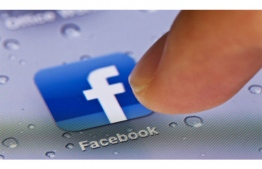 A person clicks the Facebook app icon on their mobile phone. FILE PHOTO: AFP