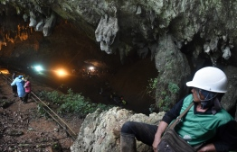 Rescue personnel are seen at the opening of the Tham Luang cave in Khun Nam Nang Non Forest Park in Chiang Rai on June 27, 2018 while operation continue for a missing children's football team and their coach. The desperate search for 12 children and their football coach trapped since June 23 in a flooded cave in northern Thailand pressed on as distraught relatives prayed and awaited news about the missing youngsters. / AFP PHOTO / LILLIAN SUWANRUMPHA