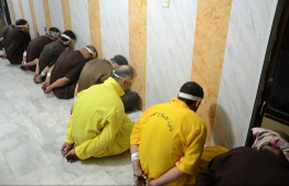 """EDITORS NOTE: Graphic content / A handout picture released by the Iraqi Justice Ministry on June 29, 2018 shows blindfolded and handcuffed jihadists of the Islamic State group who have been condemned to death waiting for their sentences to be executed. Iraq executed a dozen death row jihadists on the order of Prime Minister Haider al-Abadi, his office said today, in retaliation for the Islamic State group's execution of eight captives. The executions on June 28 came shortly after Abadi ordered the """"immediate"""" implementation of the death sentences of hundreds of convicted jihadists in response to the killings by IS.  / AFP PHOTO / Iraq Justice Minister / Handout / XGTY /  == RESTRICTED TO EDITORIAL USE - MANDATORY CREDIT """"AFP PHOTO / HO / Iraq Justice Ministry"""" - NO MARKETING NO ADVERTISING CAMPAIGNS - DISTRIBUTED AS A SERVICE TO CLIENTS =="""