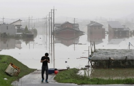 """A man stands next to a flooded residential area in Kurashiki, Okayama prefecture on July 8, 2018. Japan's Prime Minister Shinzo Abe warned on July 8 of a """"race against time"""" to rescue flood victims as authorities issued new alerts over record rains that have killed at least 48 people. / AFP PHOTO / JIJI PRESS / STR /"""