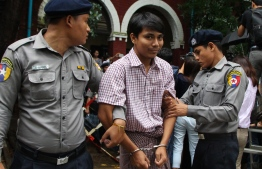 Detained Myanmar journalist Kyaw Soe Oo (C) is escorted by police to a court for his ongoing pre-trial hearing in Yangon on July 9, 2018. Two Reuters reporters accused of breaking Myanmar's draconian secrecy law during their reporting of the Rohingya crisis must face trial, a judge ruled on July 9, on a charge that carries up to 14 years in jail. / AFP PHOTO / STR