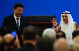 Kuwaiti ruling Emir Sheikh Sabah al-Ahmad al-Jaber al-Sabah (R) waves after giving a speech as China's President Xi Jinping (L) looks on, during the 8th Ministerial Meeting of China-Arab States Cooperation Forum at the Great Hall of the People in Beijing on July, 10, 2018. China will provide Arab states with 20 billion USD in loans for economic development, President Xi Jinping told top Arab officials on July 10, as Beijing seeks to build its influence in the Middle East and Africa. / AFP PHOTO / WANG ZHAO
