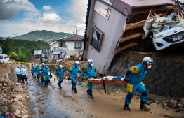 Police arrive to clear debris scattered on a street in a flood hit area in Kumano, Hiroshima prefecture on July 9, 2018. Rescue workers in Japan battled on July 9 to reach residents trapped after devastating rains that have killed at least 75 people, as authorities warned about the risk of landslides. / AFP PHOTO / Martin BUREAU