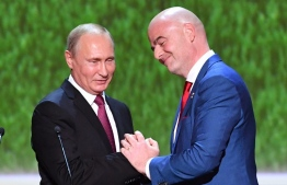 Russian President Vladimir Putin (L) shakes hands with FIFA president Gianni Infantino before a gala concert of world opera stars held at Bolshoi Theatre ahead of the 2018 FIFA World Cup Final match in Moscow on July 14, 2018. / AFP PHOTO / POOL / Yuri KADOBNOV