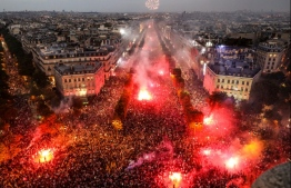 This picture taken from the top of the Arch of Triumph (Arc de Triomphe) on July 15, 2018 shows people lighting flares as they celebrate after France won the Russia 2018 World Cup final football match against Croatia, on the Champs-Elysees avenue in Paris.  / AFP PHOTO / Ludovic MARIN
