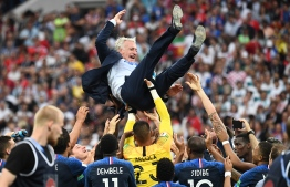 France's coach Didier Deschamps is tossed by players at the end of the Russia 2018 World Cup final football match between France and Croatia at the Luzhniki Stadium in Moscow on July 15, 2018. / AFP PHOTO / FRANCK FIFE /