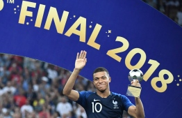 France's forward Kylian Mbappe poses with the FIFA Young Player award during the trophy ceremony at the end of the Russia 2018 World Cup final football match between France and Croatia at the Luzhniki Stadium in Moscow on July 15, 2018. / AFP PHOTO / FRANCK FIFE /