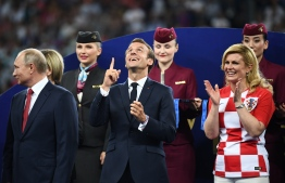French President Emmanuel Macron (C) gestures between Croatian President Kolinda Grabar-Kitarovic (R) and Russian President Vladimir Putin during the trophy ceremony at the end of the Russia 2018 World Cup final football match between France and Croatia at the Luzhniki Stadium in Moscow on July 15, 2018. / AFP PHOTO / FRANCK FIFE /