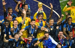 France's goalkeeper Hugo Lloris holds the trophy as he celebrates with teammates during the trophy ceremony at the end of the Russia 2018 World Cup final football match between France and Croatia at the Luzhniki Stadium in Moscow on July 15, 2018. / AFP PHOTO / Alexander NEMENOV /