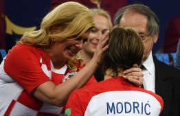 Croatian President Kolinda Grabar-Kitarovic (L) embraces Croatia's midfielder Luka Modric on the stage at the end of the Russia 2018 World Cup final football match between France and Croatia at the Luzhniki Stadium in Moscow on July 15, 2018. France won the World Cup for the second time in their history after beating Croatia 4-2 in the final in Moscow's Luzhniki Stadium on Sunday. / AFP PHOTO / Jewel SAMAD /