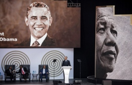 Former US President Barack Obama (R) speaks next to the Chancellor of the University of Johannesburg, Professor Njabulo Ndebele (L), South African President Cyril Ramaphosa (2ndL) and Patrice Motsepe, businessman and founder of the Motsepe Foundation, during the 2018 Nelson Mandela Annual Lecture at the Wanderers cricket stadium in Johannesburg on July 17, 2018. Former US president Barack Obama will deliver the Nelson Mandela Annual Lecture, urging young people to fight to defend democracy, human rights and peace, to a crowd of 15,000 people at the club as the centrepiece of celebrations marking 100 years since Nelson Mandela's birth. Obama has made relatively few public appearances since leaving the White House in 2017, but he has often credited Mandela for being one of the great inspirations in his life.  / AFP PHOTO / MARCO LONGARI