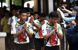 Some of the twelve Thai boys, rescued from a flooded cave after being trapped, arrive to attend a press conference in Chiang Rai on July 18, 2018, following their discharge from the hospital. The young footballers and their coach appeared healthy when they appeared before the media for the first time on July 18. / AFP PHOTO / Lillian SUWANRUMPHA