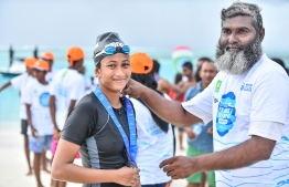Aishath Saajina is awarded a medal after winning the women's division of the National Open Water Swimming competition held in K.Dhiffushi on July 20, 2018. PHOTO: NISHAN ALI/MIHAARU