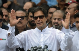 Pakistan's cricketer-turned politician Imran Khan of the Pakistan Tehreek-e-Insaf (Movement for Justice) speaks to the media after casting his vote at a polling station during the general election in Islamabad on July 25, 2018. Pakistanis voted July 25 in elections that could propel former World Cup cricketer Imran Khan to power, as security fears intensified with a voting-day blast that killed at least 30 after a campaign marred by claims of military interference. / AFP PHOTO / AAMIR QURESHI
