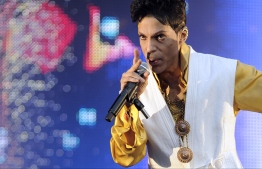 "(FILES): This June 30, 2011 file photo shows US singer and musician Prince performing on stage at the Stade de France in Saint-Denis, outside Paris.  The estate of prolific late pop icon Prince made more than 300 songs from his later career available on digital download and streaming services for the first time on Friday, August 17, 2018. The tracks come from 23 albums -- from 1995's ""The Gold Experience"" to 2010's ""20Ten"" -- that have been launched online as part of a deal struck with Sony's Legacy Recordings. There is also a new 37-track compilation called ""Prince Anthology 1995-2010,"" made up of highlights from the 23 albums.   / AFP PHOTO / BERTRAND GUAY"