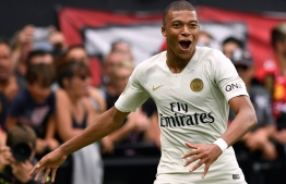 Paris Saint-Germain's French forward Kylian Mbappe celebrates after scoring during the French L1 football match between Guingamp and Paris Saint-Germain, at the Roudourou stadium in Guingamp on August 18, 2018. / AFP PHOTO / FRED TANNEAU