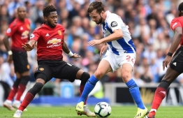 Brighton's Dutch midfielder Davy Propper (C) shields the ball from Manchester United's Brazilian midfielder Fred (L) during the English Premier League football match between Brighton and Hove Albion and Manchester United at the American Express Community Stadium in Brighton, southern England on August 19, 2018. / AFP PHOTO / Glyn KIRK / RESTRICTED TO EDITORIAL USE. No use with unauthorized audio, video, data, fixture lists, club/league logos or 'live' services. Online in-match use limited to 120 images. An additional 40 images may be used in extra time. No video emulation. Social media in-match use limited to 120 images. An additional 40 images may be used in extra time. No use in betting publications, games or single club/league/player publications. /