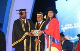 Minister of Education Aishath Shiham (R) presents the presidential award to Ahmed Abdul Matheen, who topped the Masters of Law course, at the MNU Graduation 2018.