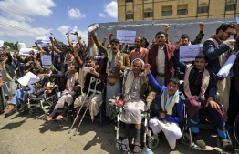 Injured Yemeni Huthi rebel fighters in seated wheelchairs and standing chant slogans during a demonstration demanding the right for the injured to travel abroad for medical treatment, outside the UN offices in the capital Sanaa on September 12, 2018. / AFP PHOTO