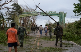 Rescue workers clear a road of debris and toppled electric posts caused by strong winds due to super Typhoon Mangkhut as they try to reach Baggao town in Cagayan province, north of Manila September 15, 2018. Super Typhoon Mangkhut slammed into the northern Philippines, with violent winds and torrential rains, as authorities warned millions in its path of potentially heavy destruction. / AFP PHOTO / TED ALJIBE