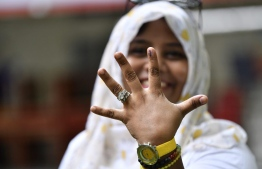 A voter showing off her finger mark after voting in the Presidential Elections 2018. PHOTO: NISHAN ALI / MIHAARU