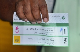 An election official shows a ballot paper during vote counting in the September 23rd Presidential Election. PHOTO/MIHAARU