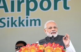 FILE PHOTO: This handout photo released by India's Press Information Bureau and taken on September 24, 2018, shows Indian Prime Minister Narendra Modi (R) addressing a gathering at the inauguration of the Pakyong Airport in Gangtok. / AFP PHOTO / PIB / Handout /
