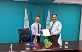 CSC's president handing over the official documents to Ahmed Latheef. PHOTO: MDP