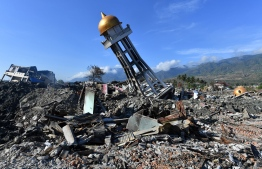 The minaret of a mosque rests to one side amongst the devastation in the hard-hit area of Balaroa in Palu on October 8, 2018, following the September 28 earthquake and tsunami. Nearly 2000 bodies have been recovered from Palu since an earthquake and tsunami struck the Indonesian city, an official said on October 8, warning the number would rise with thousands still missing. / AFP PHOTO / ADEK BERRY