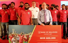 BML's managing director and CEO, Andrew Healy handing over the gift card to the national football team. PHOTO: BML