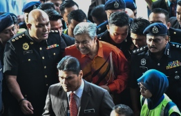 Detained Malaysia's deputy former prime minister Ahmad Zahid Hamidi is escorted by police to a court in Kuala Lumpur to face charges on October 19, 2018. - Malaysia's opposition leader, Ahmad Zahid was arrested on October 18 on suspicion of corruption, a fresh blow to his party United Malays National Organisation (UMNO), which was ousted at elections this year after six decades in power. (Photo by - / AFP) /
