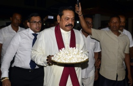 Sri Lanka's former president and new prime minister Mahinda Rajapakse arrives at a temple after having been sworn in as prime minister in Colombo on October 26, 2018. - Sri Lankan President Sirisena on October 26 sacked his Prime Minister Ranil Wickremesinghe and appointed former president Mahinda Rajapakse as the new premier, the president's office said. (Photo by LAKRUWAN WANNIARACHCHI / AFP)