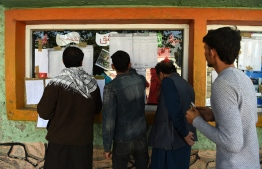 Afghan election observers check the voting results put on display at a polling centre after ballots in the country's legislative election were counted in Kabul on October 22, 2018. - Problems plagued hundreds of Afghan polling centres on October 21 in the shambolic legislative election's second day of voting, fuelling criticism of organisers and eroding hopes for credible results after a ballot marred by deadly violence. (Photo by WAKIL KOHSAR / AFP)