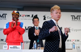 This handout photograph taken by Rizin Fighting Federation on November 5, 2018 shows Japanese kickboxer Tenshin Nasukawa (R) posing during a press conference in Tokyo to announce his fight with US boxer Floyd Mayweather Jr. - Boxing superstar Floyd Mayweather Jr. PHOTO: AFP
