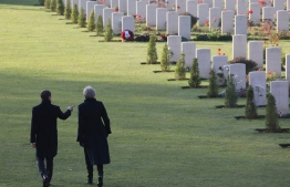 British Prime Minister Theresa May (R) and French President Emmanuel Macron walk near graves at the World War I French-British memorial of Thiepval, northern France, on November 9, 2018, during a ceremony marking the 100th anniversary of the end of the WWI. - The memorial commemorates more than 72,000 men of British and South African forces who died in the Somme sector before 20 March 1918 and have no known grave, the majority of whom died during the Somme offensive of 1916. (Photo by LUDOVIC MARIN / POOL / AFP)