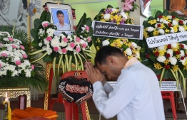 A mourner prays in front of a portrait of 13-year-old Muay Thai boxer Anucha Tasako next to his coffin during a funeral at a Buddhist temple in Samut Prakan province on November 14, 2018. - Thais have reacted with shock and anger after Tasako died during a charity bout, reviving calls for a ban on fights between children in the brutal Muay Thai martial art. (Photo by Romeo GACAD / AFP)