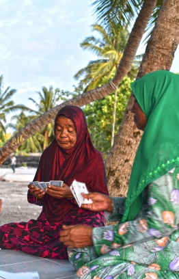 Ladies of L.Gan enjoy a round of cards at a 'holhuashi' by the harbour at sunset. PHOTO: HAWWA AMANY ABDULLA / THE EDITION