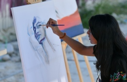 Maldha Mohamed 'Mal's Art' exhibits and paints during the 5-year anniversary show of 'Fannuge Dharin'. PHOTO: AHMED NISHAATH/MIHAARU