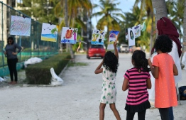 Young kids looking at paintings and drawings made by other kids at the 'Arty Fingers' stall during the 5-year anniversary show of 'Fannuge Dharin'. PHOTO: AHMED NISHAATH/MIHAARU