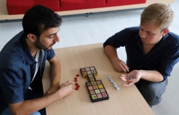 Iraqi artist Hoshmand Mofaq and British archaeologist Ashley Barlow (R) play an ancient board game, known as the Royal Game of Ur, in the northern Iraqi city of Raniey on October 22, 2018. - Originating nearly 5,000 years ago in what would become Iraq, the Royal Game of Ur mysteriously died out -- until Muwafaq resurrected it by making his own decorated wooden board. (Photo by SHWAN MOHAMMED / AFP)