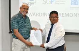 Environment Minister Dr. Hussain Rasheed (R) hands over documents to an environment programme. PHOTO: HUSSAIN WAHEED/MIHAARU