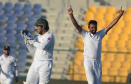 Pakistani spinner Bilal Asif (R) celebrates after taking the wicket of New Zealand batsman Tim Southee during the first day of the third and final Test match between Pakistan and New Zealand at the Sheikh Zayed International Cricket Stadium in Abu Dhabi on December 3, 2018. (Photo by AAMIR QURESHI / AFP)