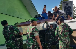 Indonesian soldiers prepare coffins for construction workers, believed to have been shot dead, in Wamena in Papua province on December 4, 2018. - Indonesia is investigating reports that 31 construction workers were shot dead by separatist rebels in restive Papua province, the public works minister said on December 4, as he halted construction in the area. (Photo by STAF STEEL / AFP)