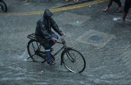 A man riding a bicycle through the heavy showers experienced by Male' City during December 2018. PHOTO: HUSSAIN WAHEED / MIHAARU