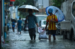 Expatriate workers on a flooded street in Male' on November 5. PHOTO: HUSSAIN WAHEED/MIHAARU