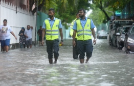 Traffic Police walk on a flooded street in Male' on November 5. PHOTO: AHMED NISHAATH/MIHAARU